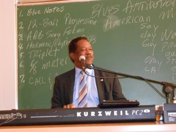 As seen on the board, various features of the blues are demonstrated on the piano.